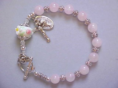 handmade rosary bracelet with rose quartz gemstones, lampworked glass, crucifix and medal dangles and toggle clasp